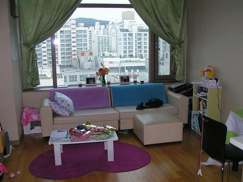 Image is of apartment, with view out of the window.  Outside, there are tall apartment buildings since Busan is a pretty crowded metropolitan.