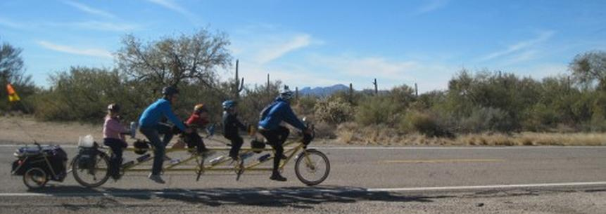 Photo is a the Pedouins on their super-tandem.  It's a long bike for five people!  Dad is in front, then the two girls, then mom, and then the third girl.  They're on a desert highway through Arizona with cactus and desert trees in the background.