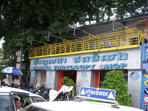 Photo is of a Cambodian printing shop taken from the street.  The shop is a small, white building with blue squiggly Cambodian script that probably says who they are.  Below the squiggly letters is the word also in blue Photocopy Shop.