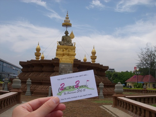 Photo is of Christi holding one of the 2B2R business cards with a Budha in the background.